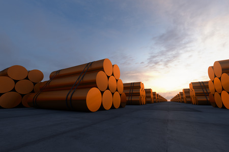 Stacks of cylindrical copper billets. In background cloudless dawn sky.