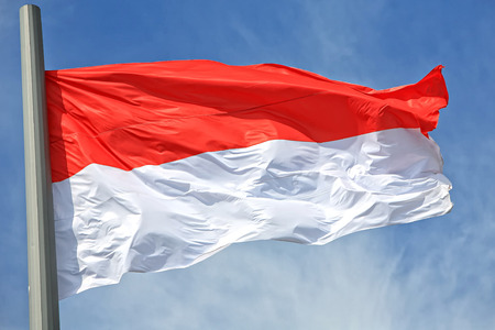 the indonesian flag: The Indonesian flag against the blue sky Stock Photo