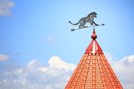 Weather vane with the image of a lion against the background of the blue sky