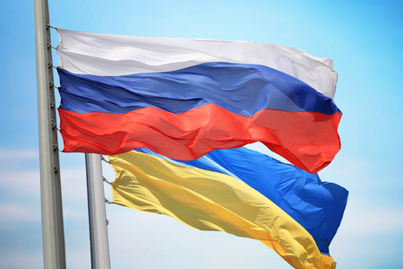 Flag of Russia and Ukraine against the background of the blue sky