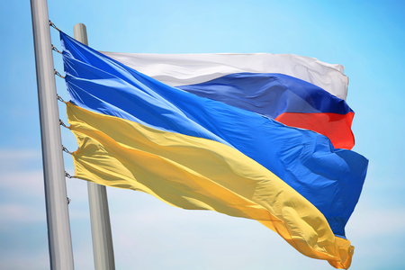 Flag of Ukraine and Russia against the background of the blue sky