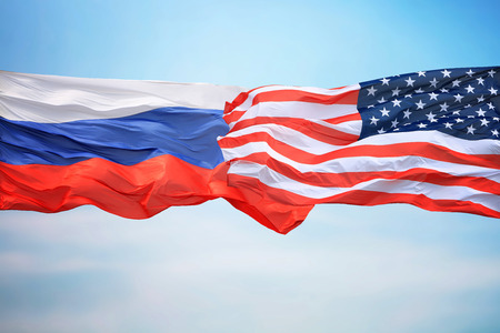 Flags of the USA and Russia against the background of the blue sky