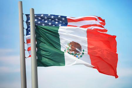 Flags of Mexico and the USA against the background of the blue sky
