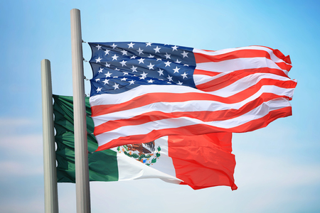 Flags of the USA and Mexico against the background of the blue sky 免版税图像