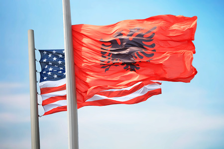 Flags of Albania and the USA against the background of the blue sky