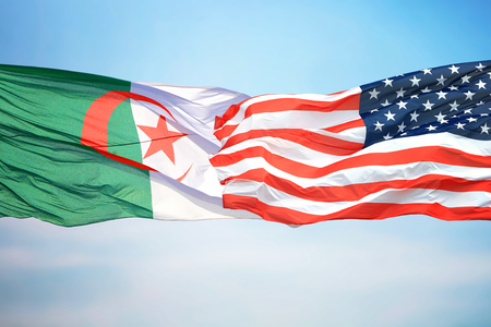 Flags of the USA and Algeria against the background of the blue sky