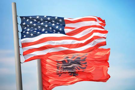 Flaggen der USA und Albaniens vor dem Hintergrund des blauen Himmels Standard-Bild