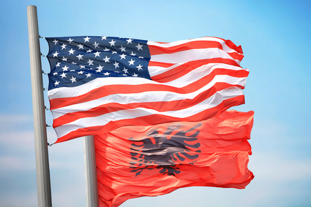 Flags of the USA and Albania against the background of the blue sky