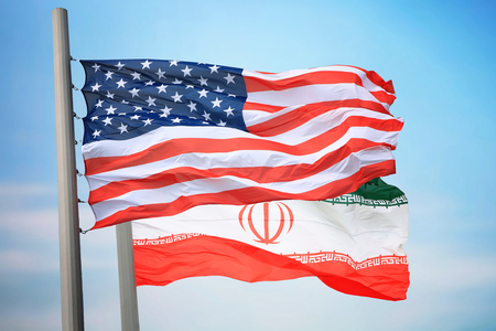 Flags of the USA and Iran against the background of the blue sky 免版税图像