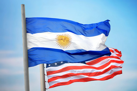 Flags of Argentina and the USA against the background of the blue sky