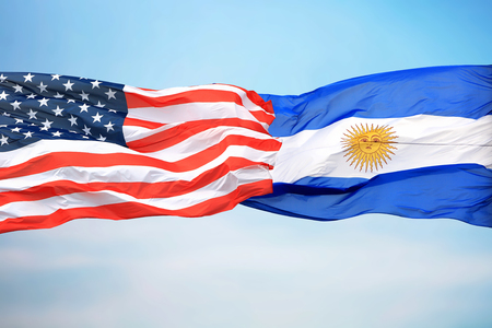 Flags of the USA and Argentina against the background of the blue sky