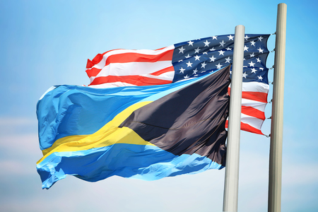 Flags of the Bahamas and the USA against the background of the blue sky