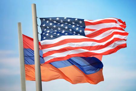 Flaggen der USA und Armeniens vor dem Hintergrund des blauen Himmels