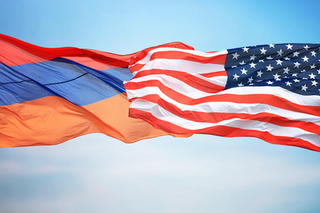 Flags of the USA and Armenia against the background of the blue sky 免版税图像
