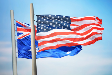 Flags of the USA and Australia against the background of the blue sky