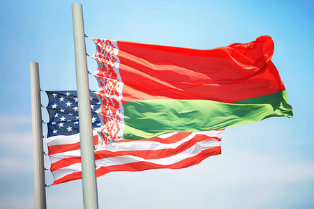 Flags of Belarus and the USA against the background of the blue sky
