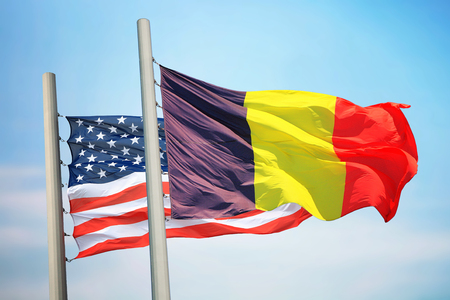 Flags of Belgium and the USA against the background of the blue sky 免版税图像