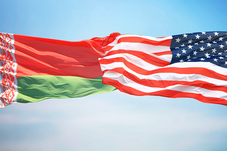 Flags of the USA and Belarus against the background of the blue sky
