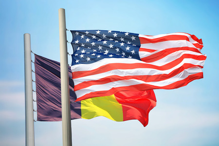 Flags of the USA and Belgium against the background of the blue sky