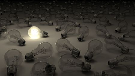 A lit light bulb surrounded by dark ones Stock Photo