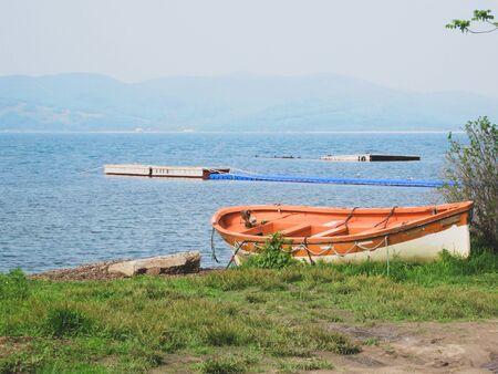 An orange fishing boat is located on the seashore. Russia, the village of Slavyanka