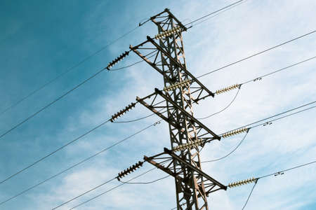 Energy distribution high voltage power line tower with wires and trees