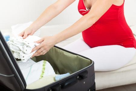 mujer con maleta: La mujer embarazada se prepara para la maternidad, empaque ropa de beb?