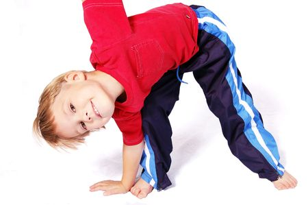 four year old: A cute four year old boy wearing red and blue bending over to touch his right toes. Stock Photo