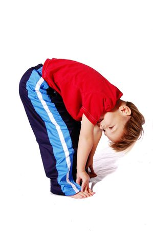 four year old: A cute four year old boy wearing red and blue who is bending over and touching his toes.