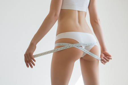 waistline: Fit young woman measuring her waistline, grey blurred background with a space for your text Stock Photo