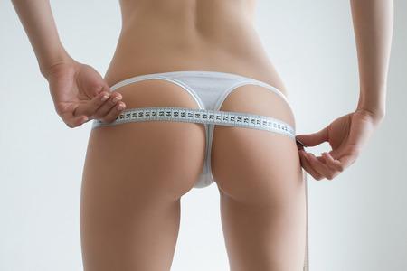 mujeres gordas: La muchacha hermosa joven mide sus partes del cuerpo de la ruleta Foto de archivo