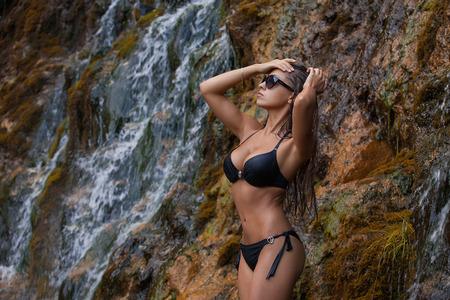 taking bath: Young and beautiful girl in bikini taking bath in a waterfall