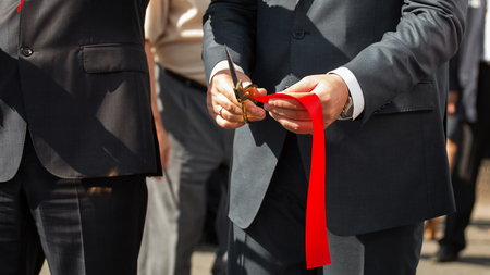 Grand opening, cutting red ribbon. Red ribbon at the opening.