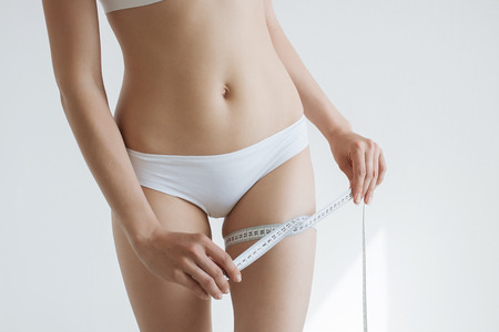 waistline: fit young woman measuring her waistline, grey blurred background with a space for your text.