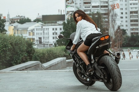 Biker girl rides a motorcycle in the rain. First-person view. 免版税图像 - 63424459