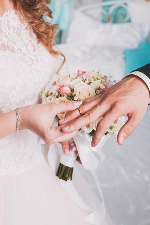 matrimony: wedding rings and hands of bride and groom. young wedding couple at ceremony. matrimony. man and woman in love. two happy people celebrating becoming family