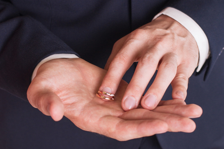 splitting up: Man is taking off the wedding ring.