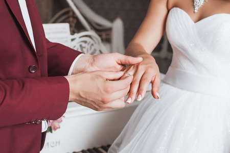 The groom places the ring on the finger of his bride Stock Photo