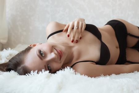 belle jeune fille en lingerie noir couché sur un fond clair Banque d'images