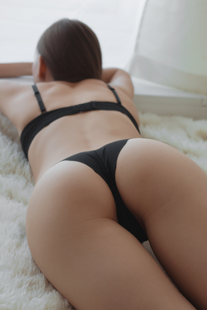Beautiful sexy lady in elegant black bodysuit. Portrait of fashion model girl indoors. Beauty woman with attractive buttocks in lace lingerie. Female ass in underwear. Naked body Stock Photo