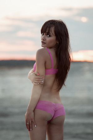 Girl in pink lingerie on the beach