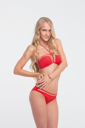 Girl with perfect body in red underwear on white background. Stock Photo