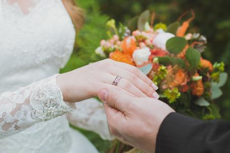 結婚指輪と新郎新婦の手。若い結婚式セレモニー。結婚。男と女の愛。2 つの幸せな人になって家族を祝う