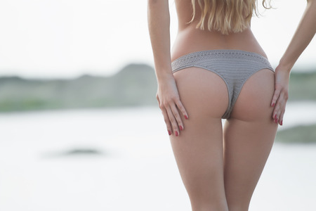 Closeup of a sexy woman's ass wearing in panties isolated on white background.