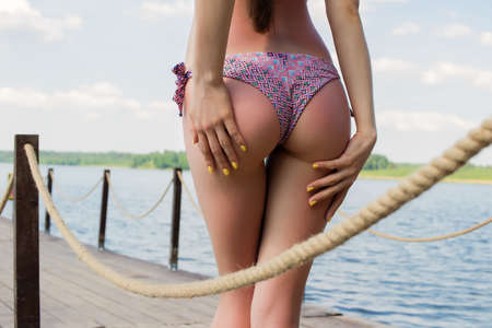 Hot woman in bikini touching buttocks Imagens