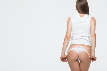 Crop back view of anonymous seductive female standing and removing thong