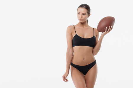 Slim lady in underwear with rugby ball