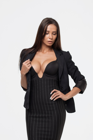 Isolated attractive sexy woman in black opened costume holding jacket and looking at camera
