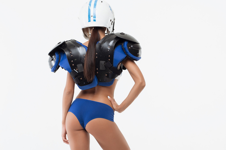 Back view of isolated sexy young woman in American football shoulder pad and helmet protection with hand on belt