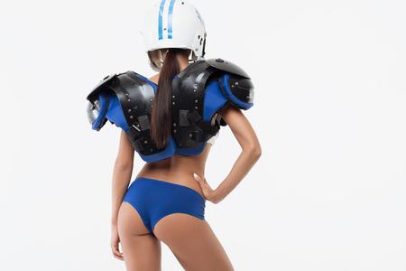 Vista posteriore della giovane donna isolata in spallina di football americano e protezione del casco con la mano sulla cintura
